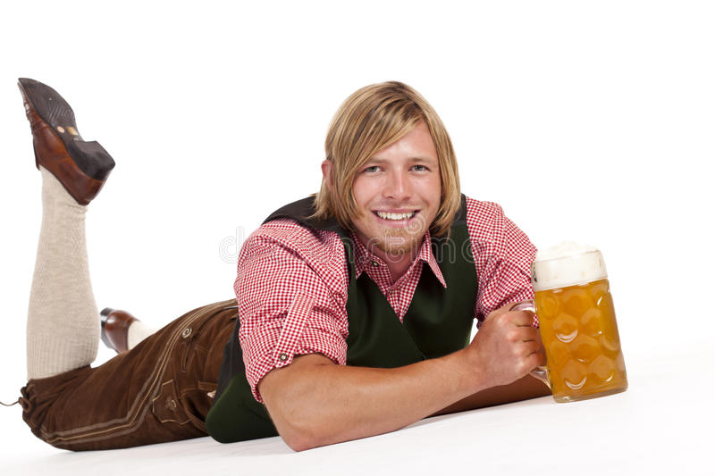 Happy man on floor holds oktoberfest beer stein royalty free stock image