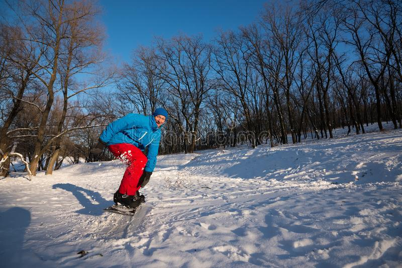 Happy man with funny face is snowboarding in the woods royalty free stock photo