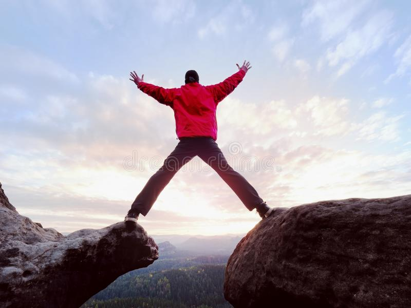 Happy man gesture of triumph with rams in air. Funny hiker on peak of rock royalty free stock photos