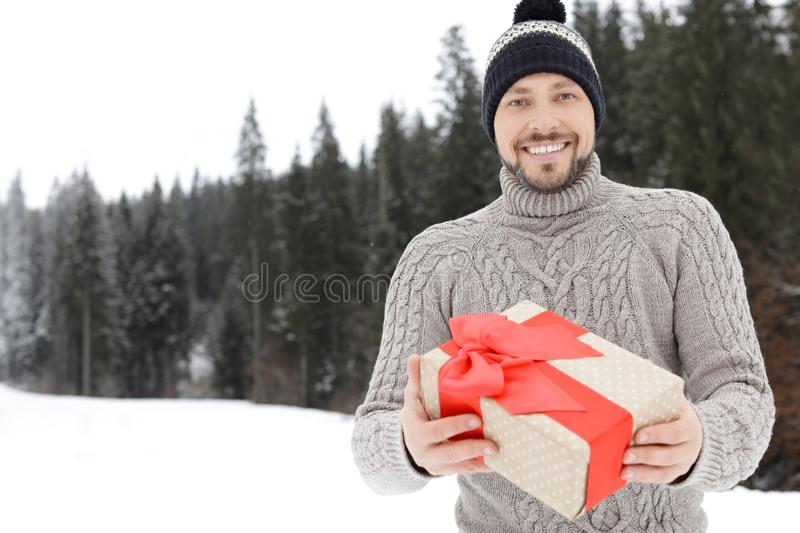 Happy man with gift box outdoors, space for text. Winter. Vacation royalty free stock photos