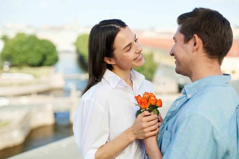 Happy man giving flowers to girlfriend royalty free stock photography