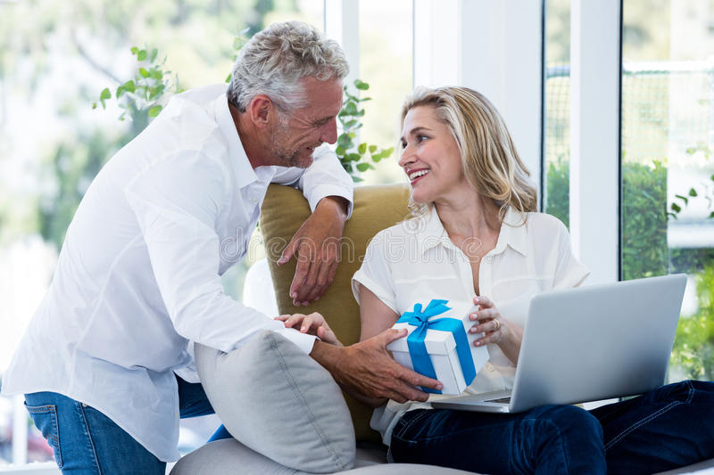 Happy man giving gift to woman with laptop royalty free stock photography