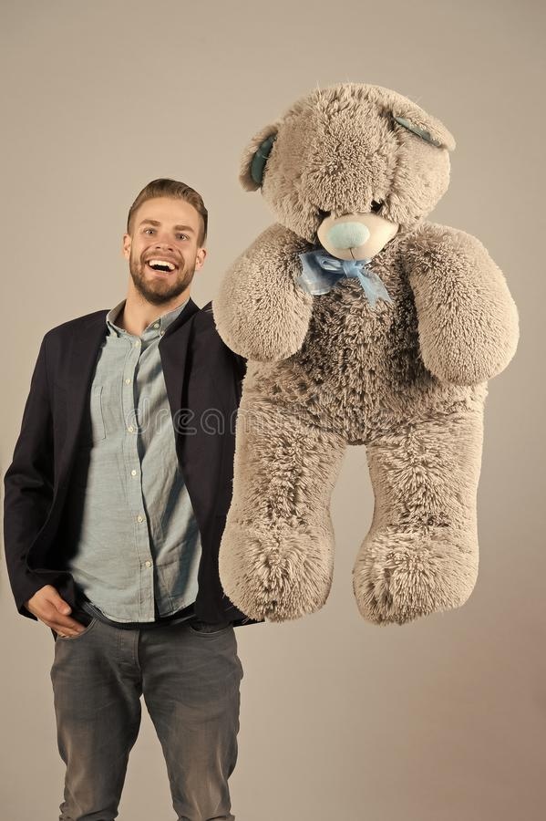 Happy man with grey teddy bear. Macho smile with big animal toy. Gift and present concept. Fashion and style. Birthday. Or anniversary and holiday celebration stock photo