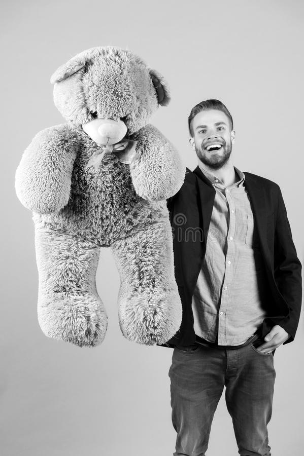 Happy man with grey teddy bear. Macho smile with big animal toy. Gift and present concept. Fashion and style. Birthday. Or anniversary and holiday celebration stock photography