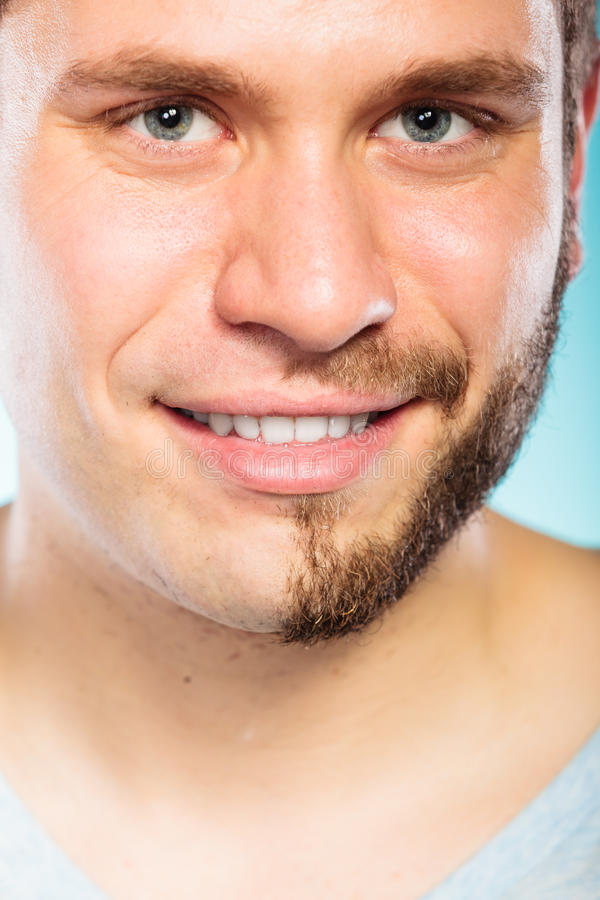Happy man with half shaved face beard hair. Closeup of happy man with half shaved face beard hair. Smiling handsome guy on blue. Skin care and hygiene stock image