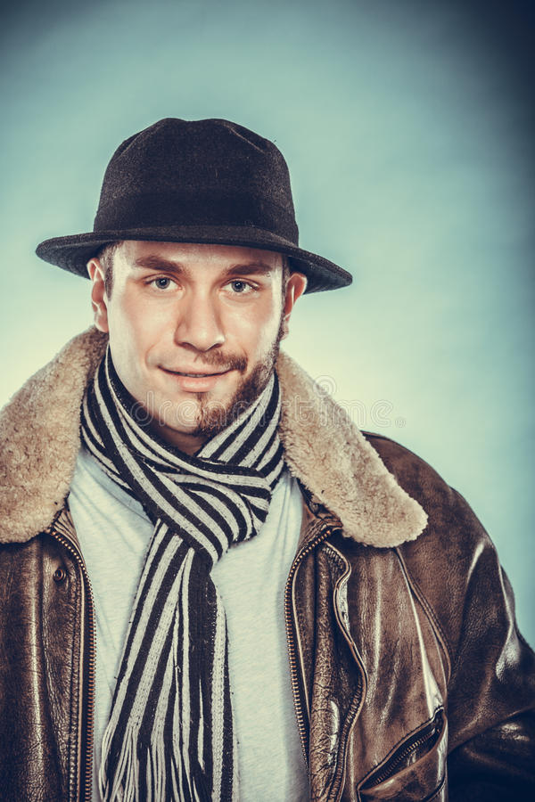 Happy man with half shaved face beard hair in hat. Portrait of happy man with half shaved face beard hair in hat, scarf and jacket. Smiling handsome guy on blue stock photos