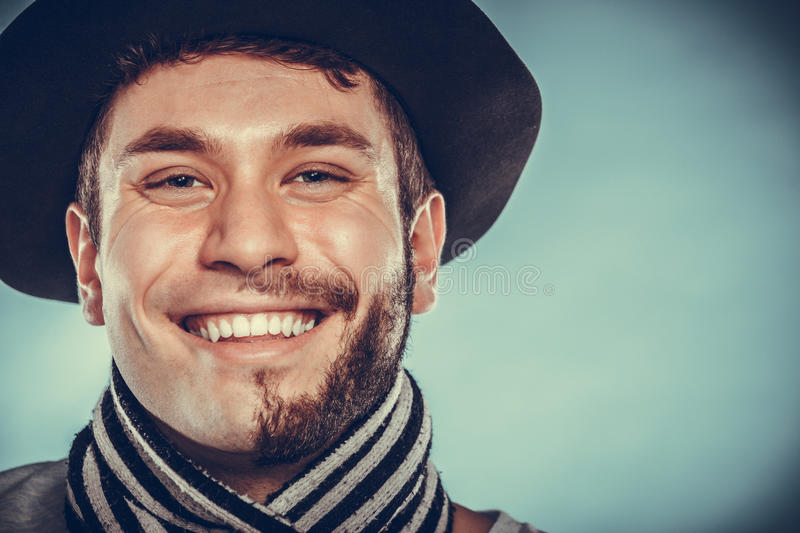 Happy man with half shaved face beard hair in hat. Portrait of happy man with half shaved face beard hair in hat and scarf. Smiling handsome guy on blue. Skin royalty free stock image