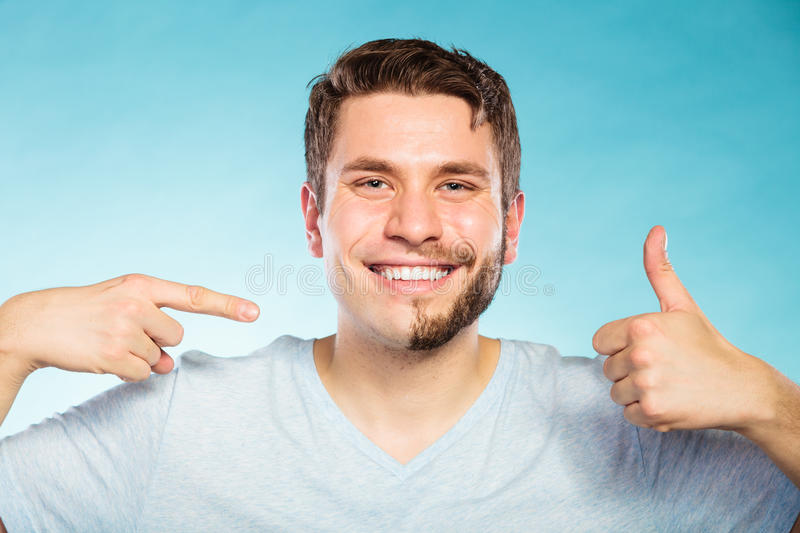 Happy man with half shaved face beard hair. Portrait of happy man with half shaved face beard hair. Smiling handsome guy on blue showing thumb up gesture. Skin stock image