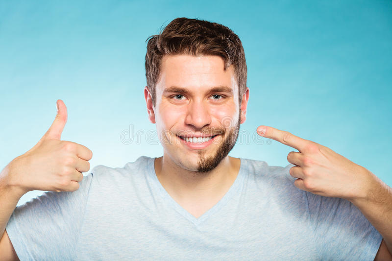 Happy man with half shaved face beard hair. Portrait of happy man with half shaved face beard hair. Smiling handsome guy on blue showing thumb up gesture. Skin stock images