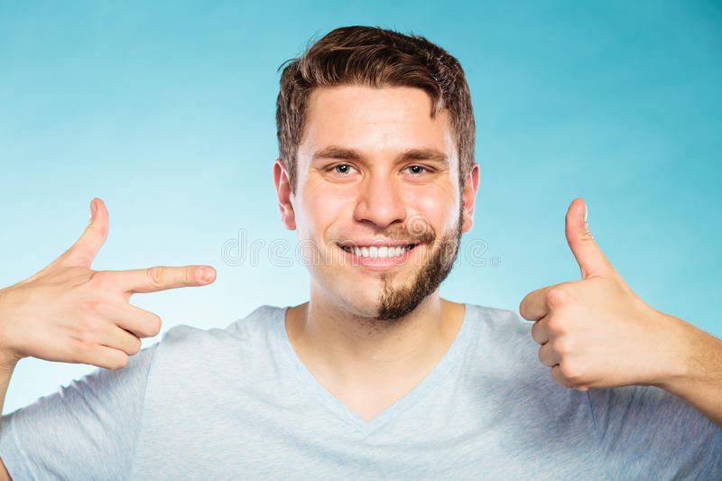 Happy man with half shaved face beard hair. Portrait of happy man with half shaved face beard hair. Smiling handsome guy on blue showing thumb up gesture. Skin royalty free stock photo