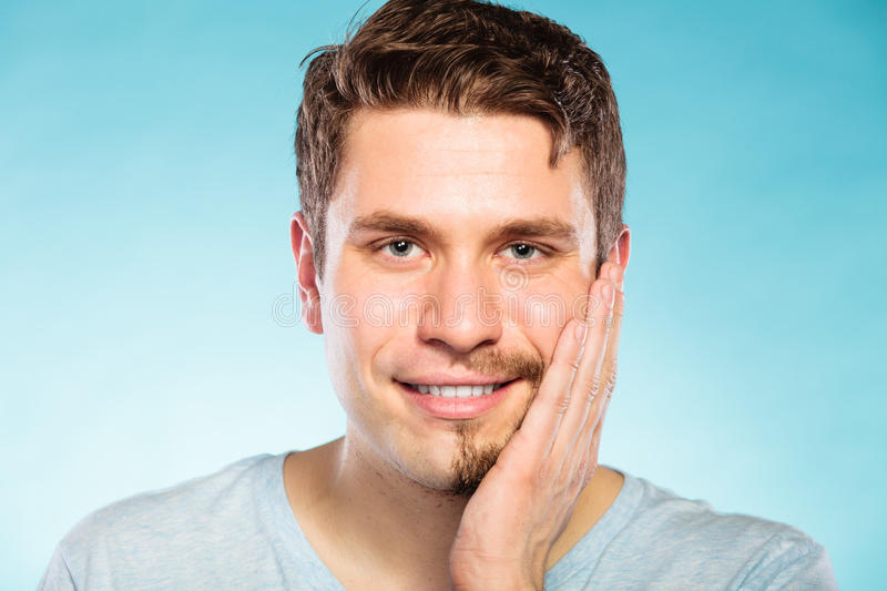 Happy man with half shaved face beard hair. Portrait of happy man with half shaved face beard hair. Smiling handsome guy on blue. Skin care and hygiene stock images