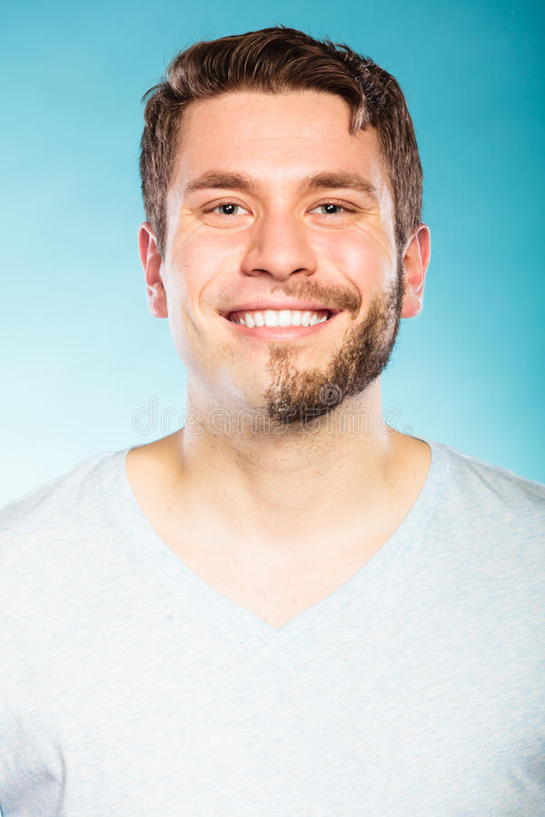 Happy man with half shaved face beard hair. Portrait of happy man with half shaved face beard hair. Smiling handsome guy on blue. Skin care and hygiene stock photo