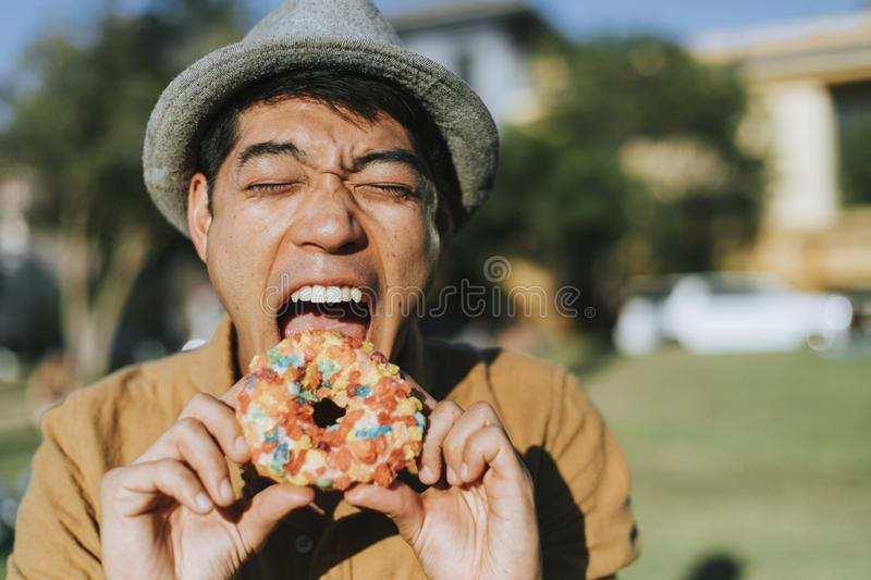 Happy man having a doughnut royalty free stock photography