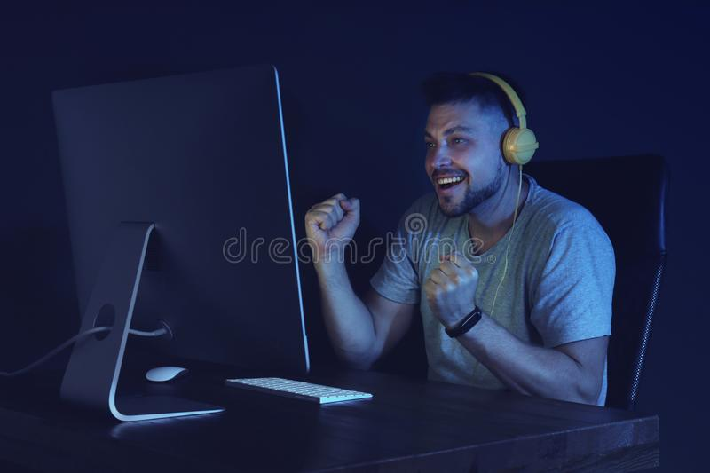 Happy man with headphones playing video game on modern computer stock photography