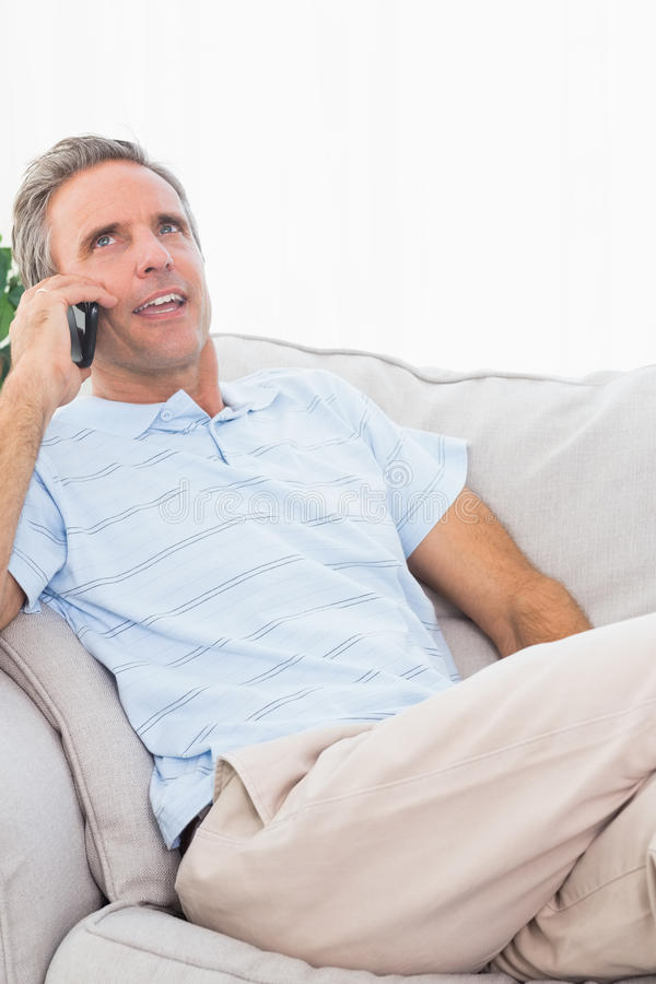 Happy man on his couch making phone call. At home on couch stock image