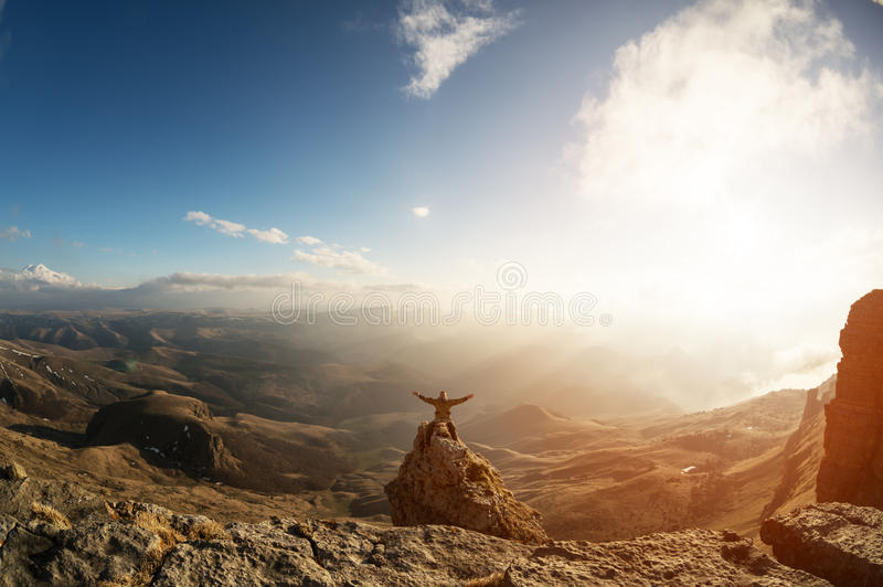 A happy man with his hands up high stands on top of a separately standing rock that is above the clouds against the stock image