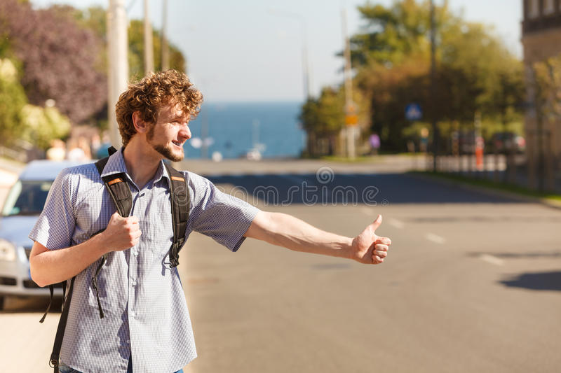 Happy man hitchhiking on summer vacation. Young man hitchhiking on summer vacation. Happy guy tourist beside road with thumb up gesture having fun stock photos