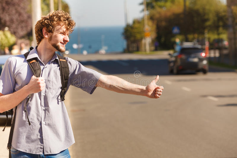 Happy man hitchhiking on summer vacation. Young man hitchhiking on summer vacation. Happy guy tourist beside road with thumb up gesture having fun royalty free stock image