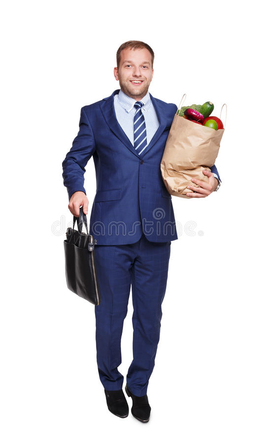 Happy man hold bag with healthy food, grocery buyer isolated. Smiling young businessman hold shopping paper bag full of groceries, vegetables and fruits, and stock photos