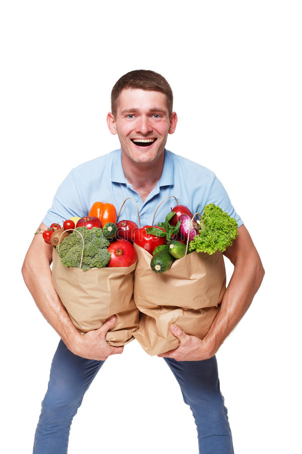 Happy man hold bags with healthy food, grocery buyer isolated. Smiling young man holding shopping bags full of groceries isolated at white background. Healthy royalty free stock photos
