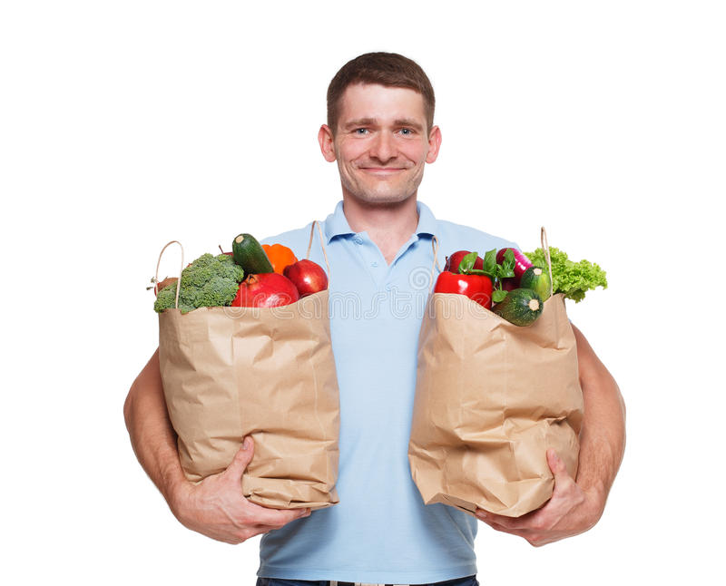 Happy man hold bags with healthy food, grocery buyer isolated. Smiling young man holding shopping bags full of groceries isolated at white background. Healthy stock image