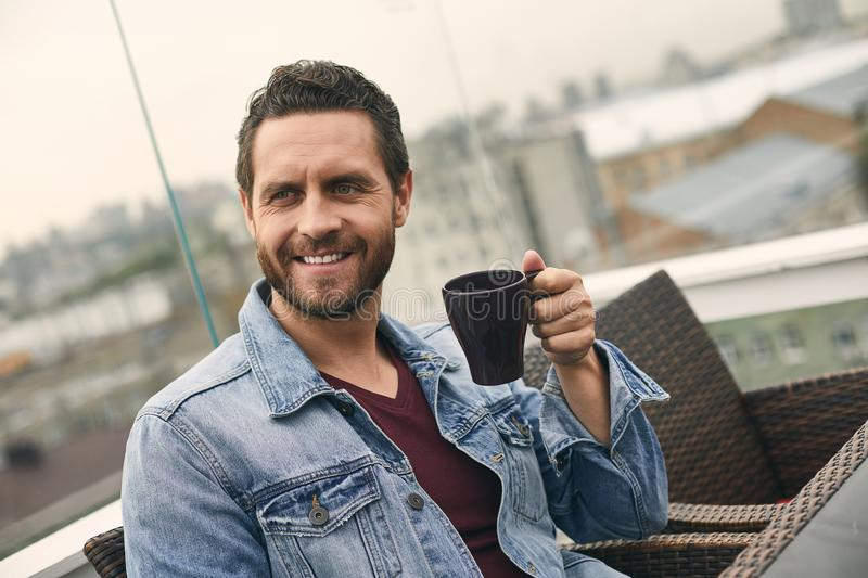Happy man is holding cup in hand stock image