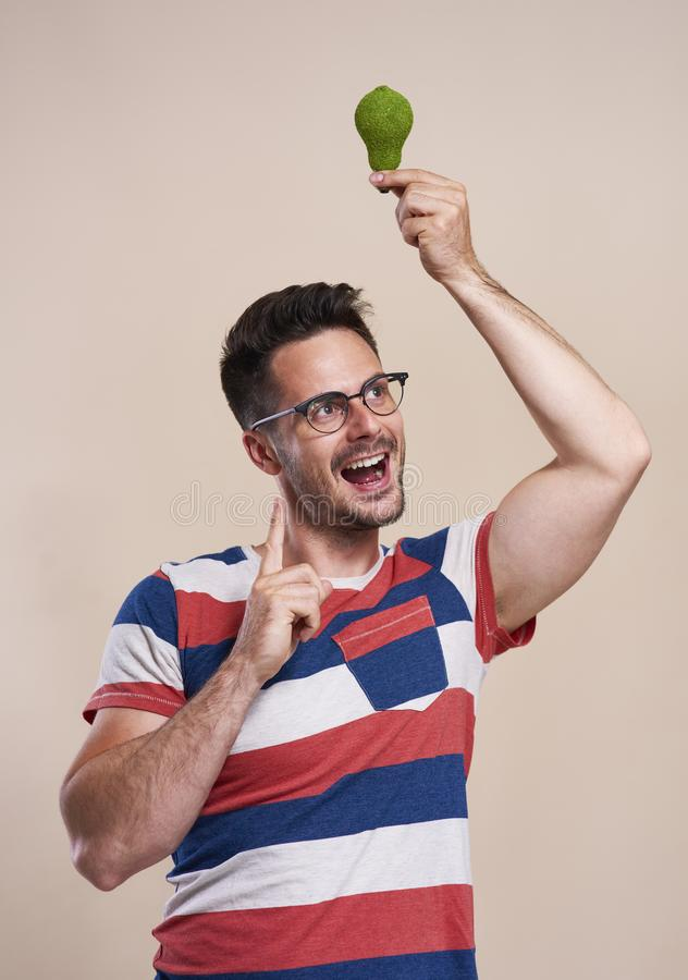 Happy man holding a energy efficient light bulb. In studio shot stock photos