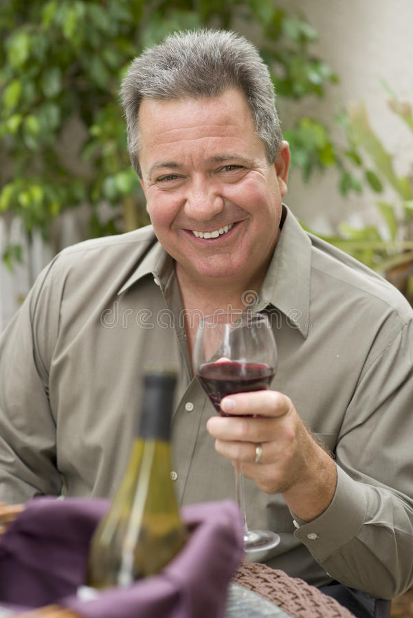 Happy Man Holding Glass of Wine. A happy smiling middle-aged man, whose hair is turning gray, is enjoying the afternoon outside in a garden, holding a glass of stock photo