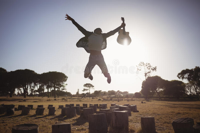 Happy man holding guitar while jumping against clear sky royalty free stock images
