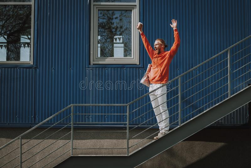 Happy man holding hands up on outdoor stairs. Urban lifestyle concept. Full length side on portrait of young happy excited hipster man with cup of coffee holding stock photos