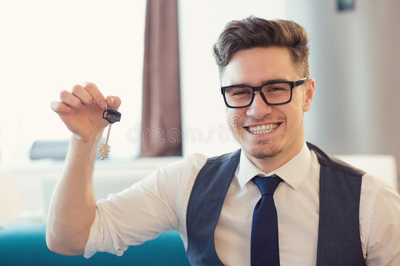Happy man holding key of new apartment. Young smiling man in eyeglasses holding key from new house sitting on couch royalty free stock images