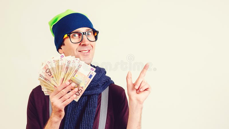 Happy man holding money banknotes. Funny guy pointing on copy space. Hipster man in glasses wearing hat with money royalty free stock photography