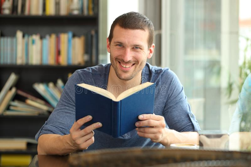 Happy man holding a paper book posing looking at camera. Front view portrait of a happy man holding a paper book posing looking at camera sitting in a coffee royalty free stock image