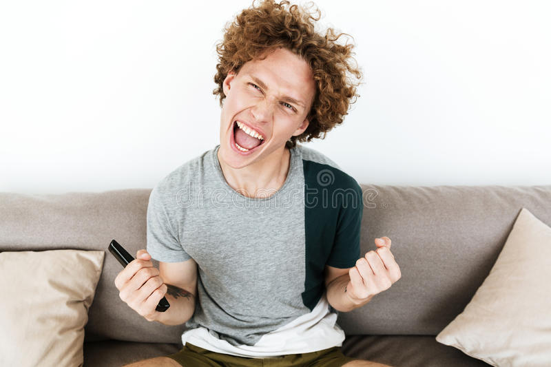 Happy man holding remote control make winner gesture royalty free stock images