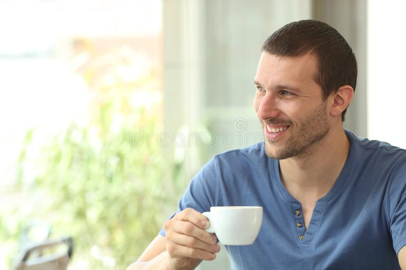 Happy man holds a coffee cup looking through a window royalty free stock image
