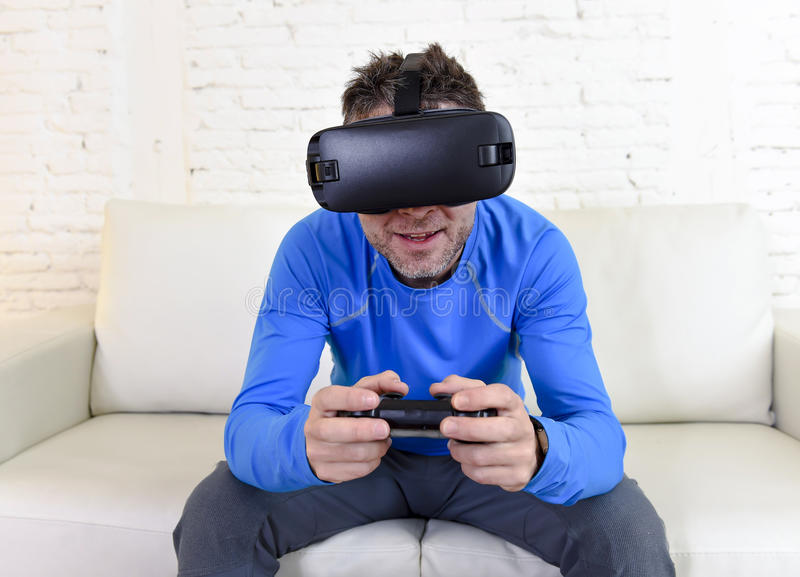 Happy man at home living room sofa couch excited using 3d goggles watching 360 virtual reality. Young modern man at home living room sofa couch playing video royalty free stock images