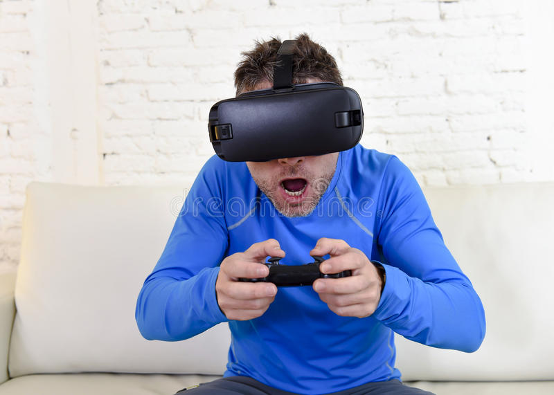 Happy man at home living room sofa couch excited using 3d goggles watching 360 virtual reality. Young modern man at home living room sofa couch playing video royalty free stock photo