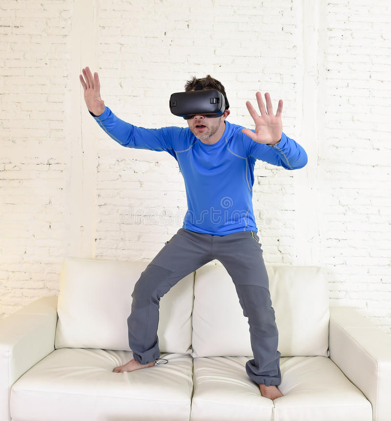 Happy man at home living room sofa couch excited using 3d goggles watching 360 virtual reality. Young modern man at home standing on living room sofa couch stock image