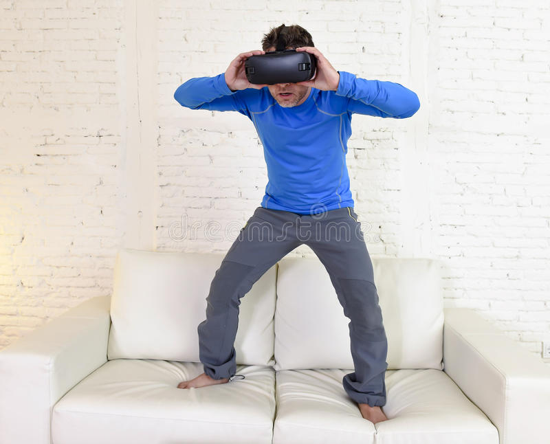 Happy man at home living room sofa couch excited using 3d goggles watching 360 virtual reality. Young modern man at home standing on living room sofa couch royalty free stock images