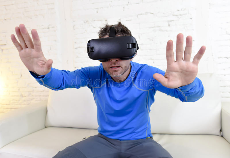 Happy man at home living room sofa couch excited using 3d goggles watching 360 virtual reality. Young modern man at home living room sofa couch excited using 3d royalty free stock photos