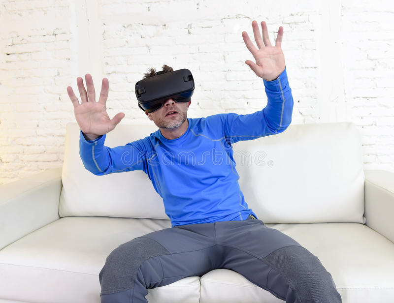 Happy man at home living room sofa couch excited using 3d goggles watching 360 virtual reality. Young modern man at home living room sofa couch excited using 3d stock photography