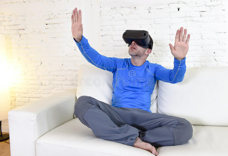 Happy man at home living room sofa couch excited using 3d goggles watching 360 virtual reality. Young modern man at home living room sofa couch excited using 3d stock photo