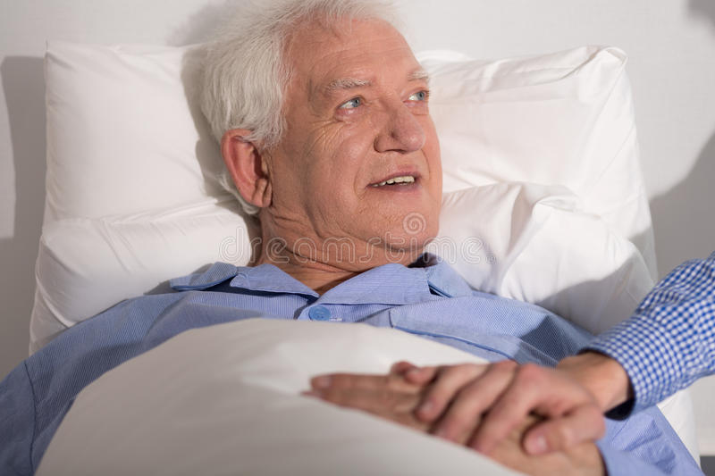 Happy man in hospital. Happy aged men having a guest in hospital royalty free stock images