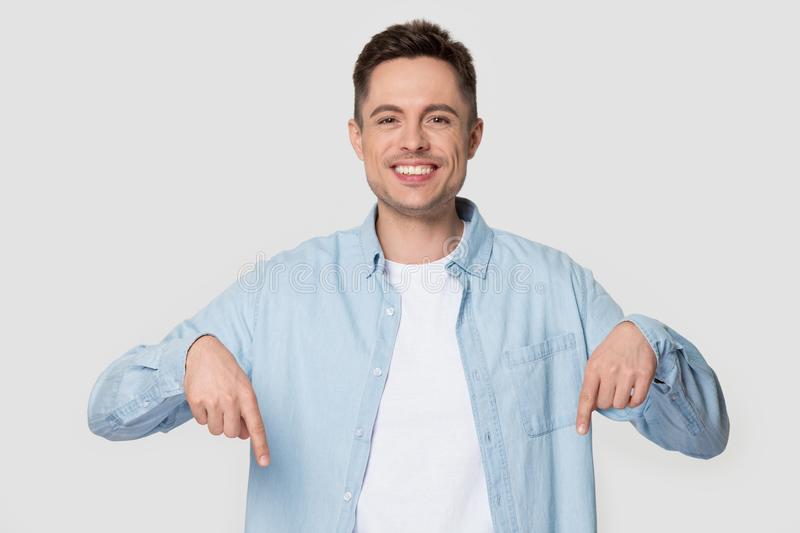 Happy man isolated on grey background pointing fingers down stock photos
