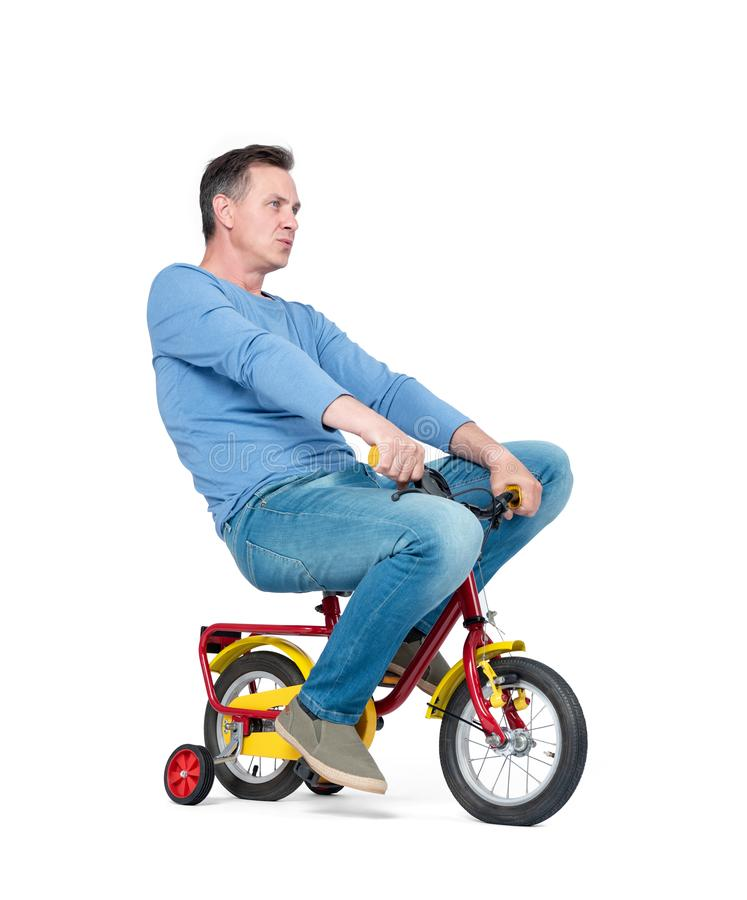 Happy man in jeans and t-shirt on a children`s bike, isolated on white background. stock photography
