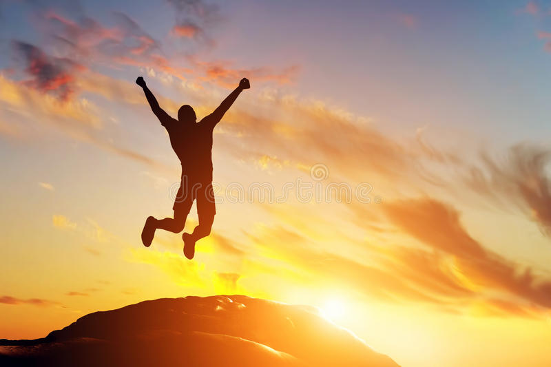 Happy man jumping for joy on the peak of the mountain at sunset. Success royalty free stock photos