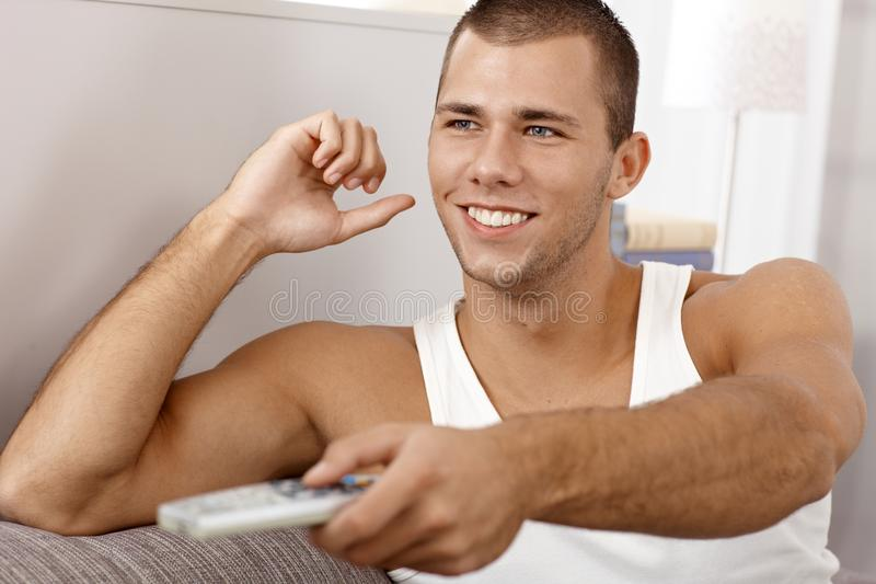 Happy man laughing with remote control royalty free stock photography