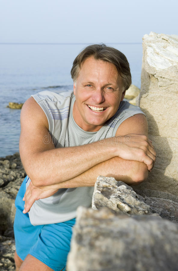 Happy man leaning on a rock royalty free stock photography