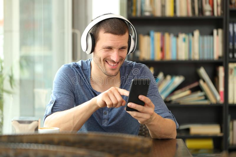 Happy man listening to music with headphones and phone. Happy man listening to music with headphones and smart phone sitting in a coffee shop stock image