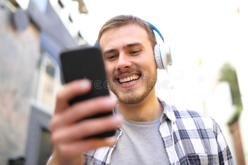 Happy man listens to the music walking in the street royalty free stock image